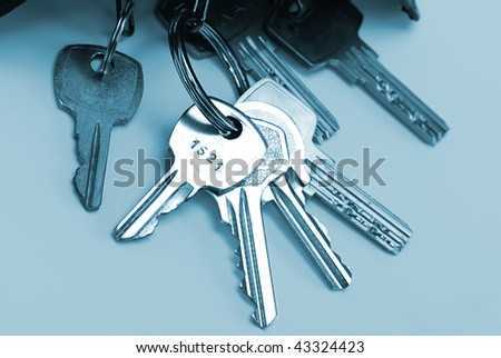 Bunch of keys isolated over blue background - stock photo
