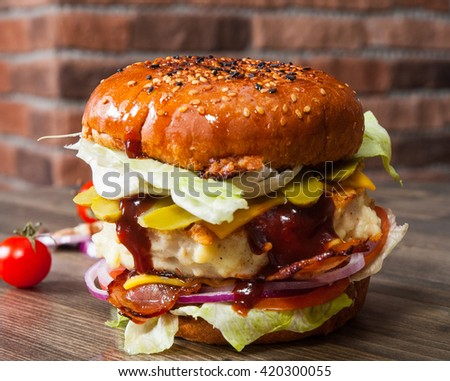 burger on wooden table against the background of a brick wall