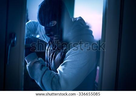 burglar with crowbar to break door to enter the house - stock photo