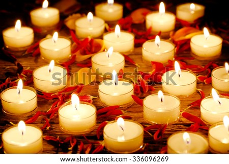 burning candles with flower petals on wooden surface - stock photo