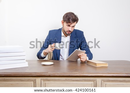 Business concept - handsome man with beard and brown hair and blue suit and tablet pc computer and some books and cup drinking coffee or tea sitting in the office.  Isolated on white background.   - stock photo