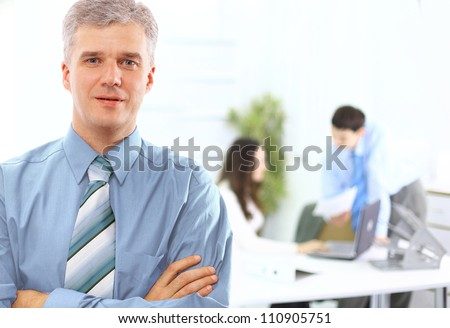 business executive - Mature business man with his colleagues in the background - stock photo