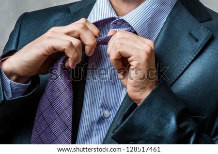 business man in suit untying his neck tie - stock photo