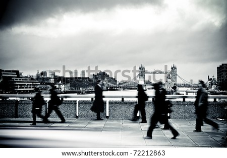 business man stands still against against on coming city workers - stock photo