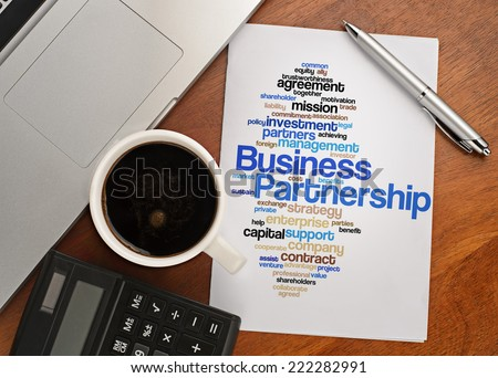 """BUSINESS PARTNERSHIP word cloud arrangement"" Notebook with text vision on table with coffee, calculator and notebook - stock photo"