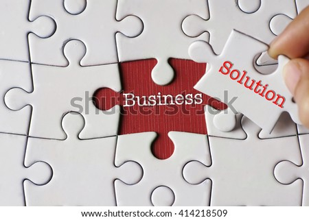 """""""Business"""" text on missing puzzle with a hand hold a piece of  """"Solution"""" text puzzle want to complete it  - stock photo"""