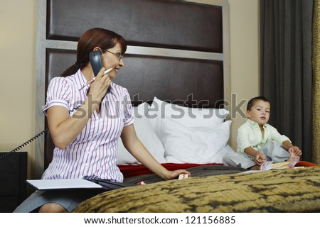business woman looking at son while communicating on phone in bedroom - stock photo