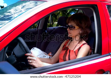 business woman smiling and driving a brand new car