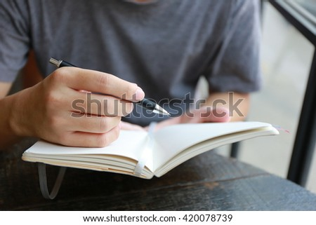 businessman hand write pen on paper,hand writing pen on paper page,hardworking for achievement business target concept, write idea by pen. - stock photo