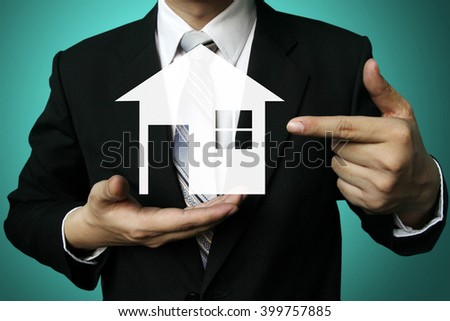 businessman hold house concept ,real estate concept - close up of business man holding small house in his hands