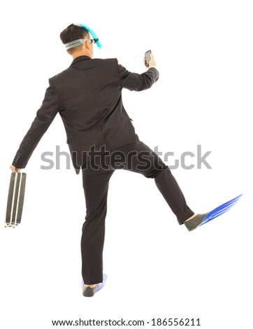 businessman holding a briefcase and watching smart phone