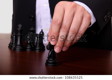 businessman is moving a chess piece - stock photo