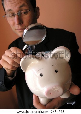 Businessman  looks to piggy bank through a magnifying glass - stock photo