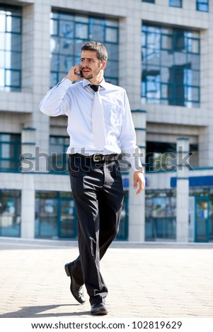 businessman talking on his cellphone while walking outdoors in front of a modern office building - stock photo