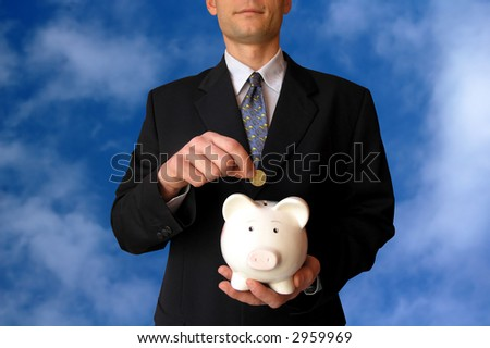 Businessman with a piggy bank on sky background.He puts coin in a piggy bank. - stock photo