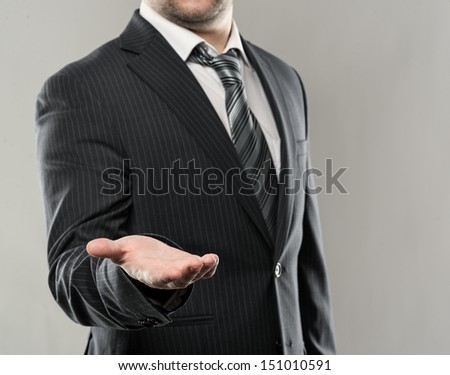 Businessman with open palm offering something. Close-up of young businessman's hand in concept of holding or giving.   - stock photo