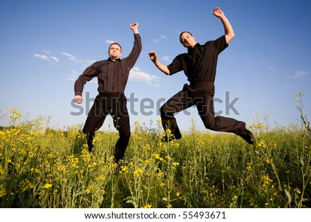 businessmans jumping in rapeseed - stock photo
