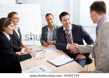 Businesspeople shaking hands in skyscraper office after meeting.