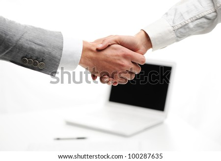 businesspeople shakinghand in office, laptop on background - stock photo