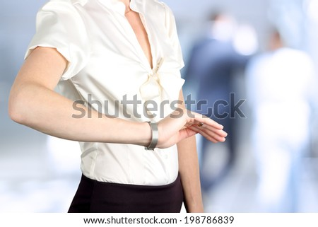 businesswoman checking time on her watch at office