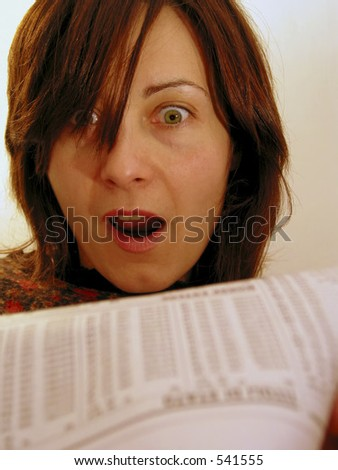 Businesswoman happy and surprised while reviewing her stocks in a financial newspaper