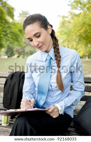 businesswoman making note in park,  overworked - stock photo