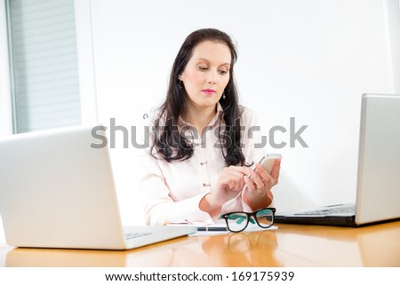 businesswoman phoning in the office,sends a message - stock photo