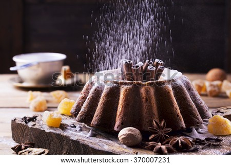 Cake with ginger, cinnamon, clove and star anise on dark old wooden background. - stock photo