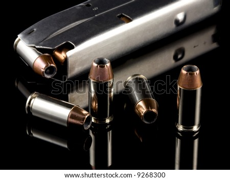 40 caliber bullets and clip on black reflective background - stock photo