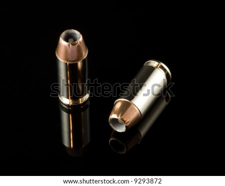 2 40 caliber bullets on a black reflective background - stock photo