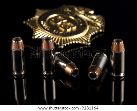 40 caliber bullets with a gold badge on a black reflective background. - stock photo