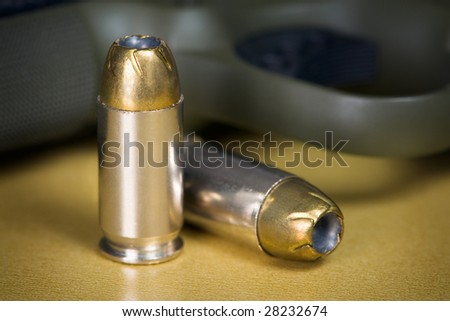 .45 Caliber Hollow Point Pistol Bullets Standing Near Handgun on gold colored background - stock photo
