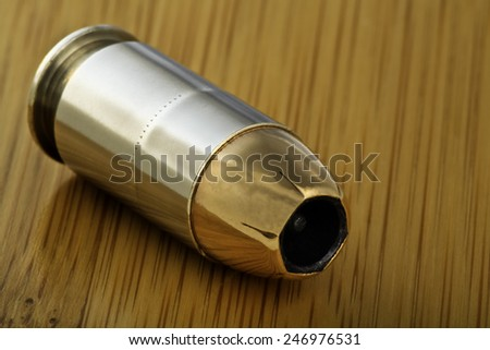 45 caliber jacketed hollow point bullet cartridge live round for semi-automatic handgun gun, bamboo wood background - stock photo