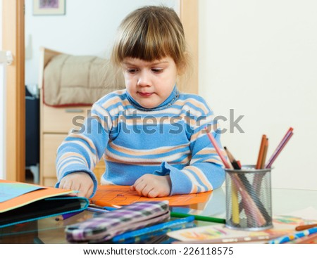 calm three year child sketching on paper in home interior - stock photo