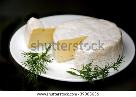 Camembert on the plate with fresh parsley isolated on black background.
