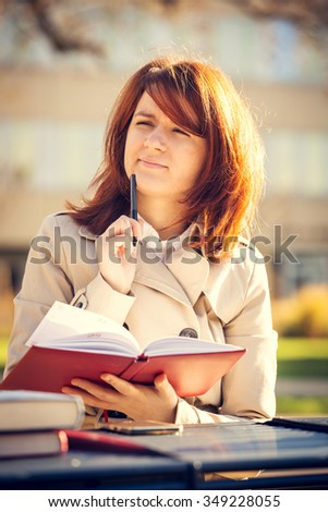 Campus.Portrait of a student thinking sitting on university bench outside studying with pen and book journal.Young business woman thinking writing diary at city park. Student. - stock photo