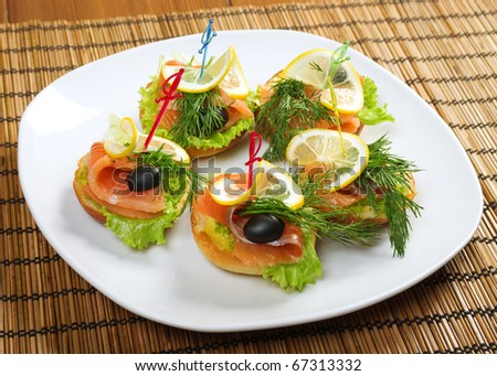 Canapes with Smoked Salmon and lemon on plate