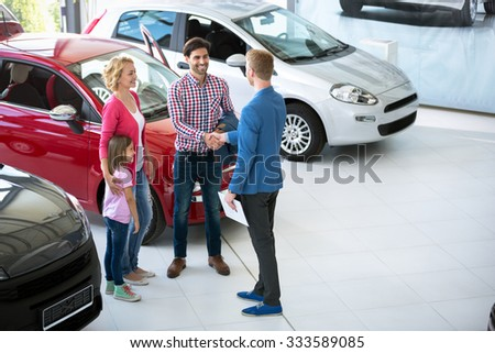 car salesman showing new vehicle to family customers - stock photo