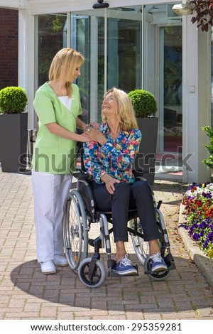 Caring Blond Nurse Standing with Hand on Shoulder of Senior Woman Sitting in Wheelchair Outdoors in front of Building on Sunny Day. - stock photo