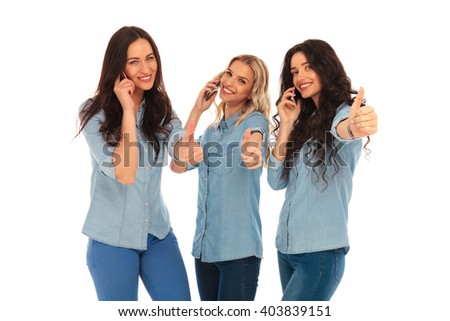 3 casual women talking on the phone making the ok thumbs up hand sign on white studio backogrund - stock photo