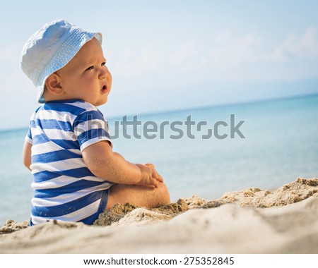 caucasian baby boy with a hat sitting on sand - stock photo