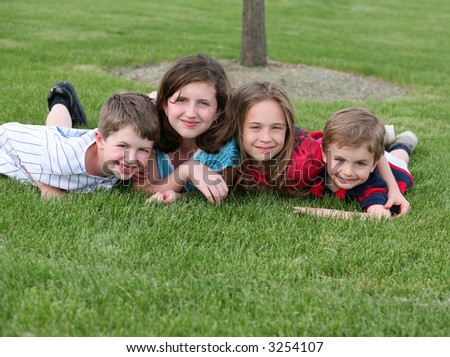 4 caucasian children smiling and laying in grass