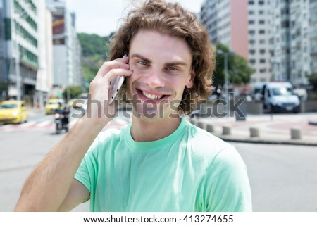 Caucasian guy with long hair at phone - stock photo