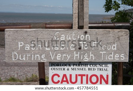 """Caution Path Liable to Flood During Very High Tides"" Sign on Porlock Beach on the South West Coastal Path between Minehead and Porlock Weir in Somerset, England, UK. - stock photo"