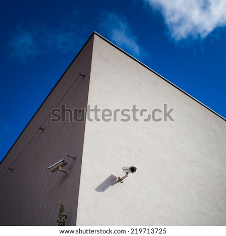 2 CCTV cameras on the corner of modern building (against blue sky, colorful image) - stock photo