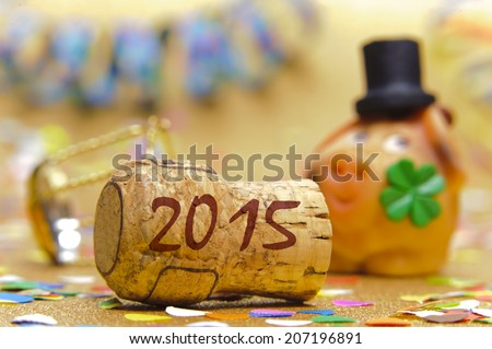 champagne cork marked with year 2015 in front of pig with cloverleaf as symbol for good luck - stock photo