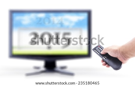 2014-2015 change represents the new year 2015. Human hand holding remote and out of focus TV LCD monitor isolated on white. - stock photo