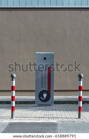 """Charging station for electric cars"" written in German in the streets in the sun"
