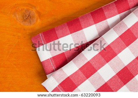 checkered napkin on wooden table - stock photo
