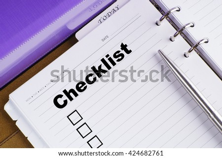 """Checklist"" text on notebook on a wooden table with open diary and pen - conceptual images"